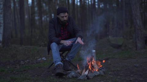 Bearded man sit in the forest near bonfire and put beverage in a cup from Live Action