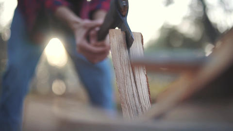 A man in plaid shirt and jeans chops wood in two pieces. Forester cuts wood Footage
