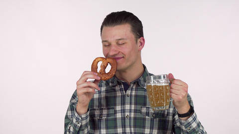 Cheerful young man holding mug of beer, smelling delicious pretzel Footage
