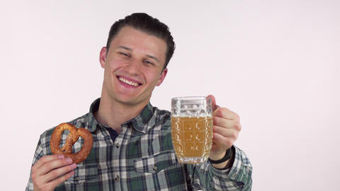 Handsome cheerful man holding out delicious beer in a mug to the camera Footage