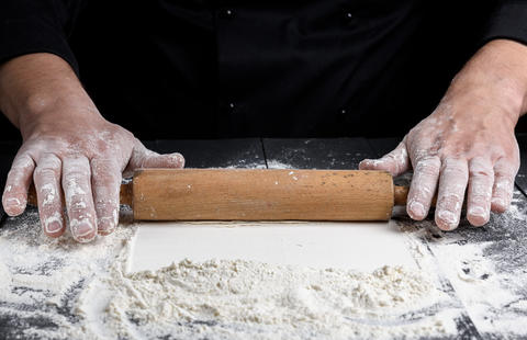wooden rolling pin in male hands フォト