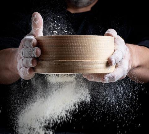 man sifts white wheat flour through a wooden sieve フォト