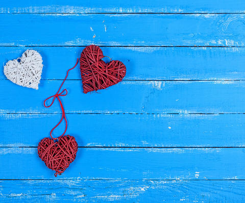 wicker hearts on a blue wooden plank background Photo