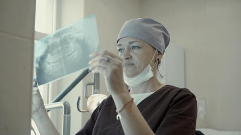 Woman dentist looking x-ray jaw Live Action