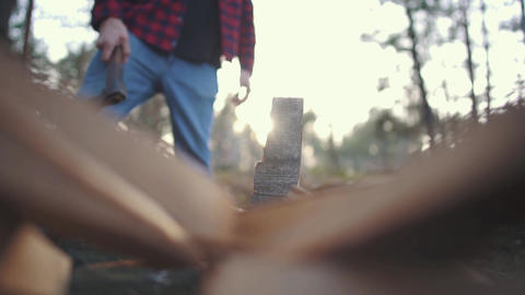 A guy chops wood with axe in forest. Slow motion ビデオ