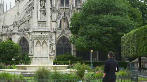 Stylish man enjoying view of beautiful Notre-Dame Cathedral, sightseeing tour Live Action
