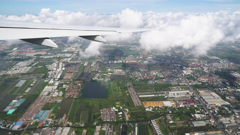 The airplane flies through the clouds above the earth, city roads and rooftops Footage