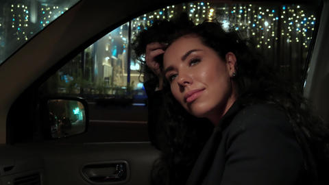 A curious young beautiful woman looks at the night city through the car window ビデオ