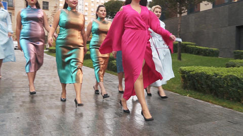 Beautiful girls in fashion dresses defile on the street. Plus size Fashion Week Live Action