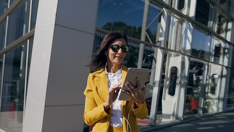 Portrait shot of the Caucasian young businesswoman in suit working on the tablet Footage