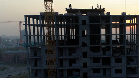 Silhouettes of builders on the construction of the house in the evening Archivo