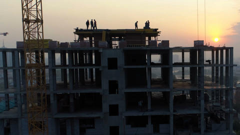 Silhouettes of builders on the construction of the house in the evening Footage