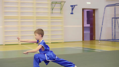 Young caucasian boy in national Chinese dress is practicing Kung Fu wushu tai GIF
