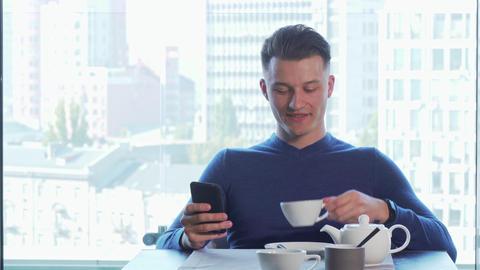Cheerful handsome man smiling joyfully, using his smart phone, drinking tea Footage
