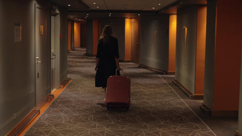 Hotel guest with trolley case walking to the room Footage