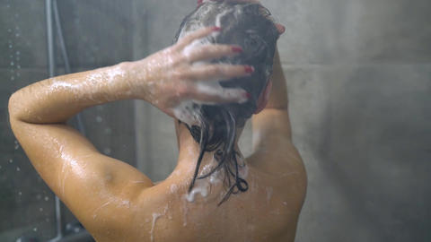 Woman washing her hair with shampoo. Hair care, beauty and wellbeing concept Live Action