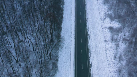 Aerial view of traffic on the road passing through the winter forest in severe Live Action