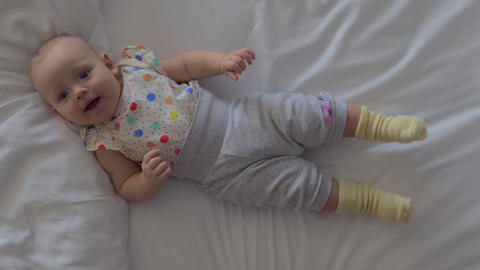 A smiling six months baby girl lying on a bed Live Action