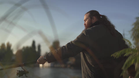 Bearded fisherman fishing on the river. Fisher stands on the river bank with the Live Action