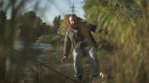 Fisherman runs to the rod and grabs it, but fish escapes. Bearded man is fishing Live Action