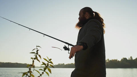 Fisherman throws fishing rod into the water. Man fishing with fishing rod. River Live Action