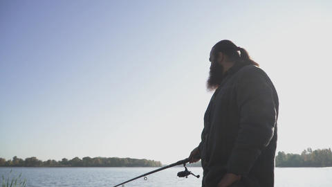 Man with beard is fishing on the river bank. Fisherman fishing with a fishing Live Action