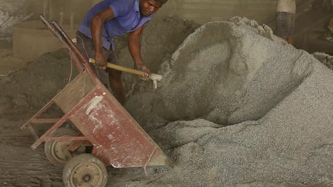 shovels with cement shift raw cement into a wheelbarrow Live Action