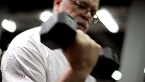 Old grizzled man with dumbbells Footage