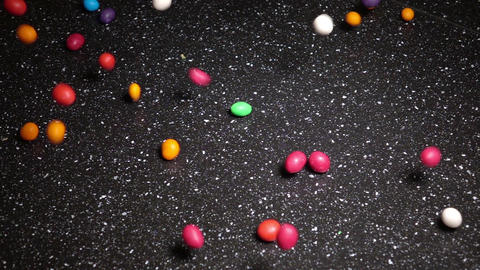 Multicolor Candy Falling Down on Black Table, slow motion Footage