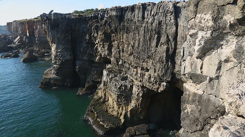 Calm sea and high rocky cliffs with light waves rolling against, cave in cliffs Footage