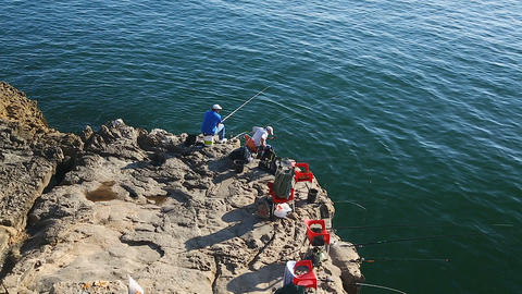 Men fishing on low cliff, chairs standing along cliff edge, recreation activity Live Action