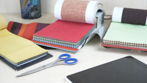 Workplace of tailor with fabric samples of different colors on table Footage