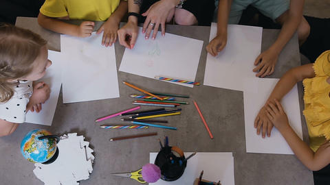 Top view, a group of elementary school kindergarten children taking pencils draw Live Action