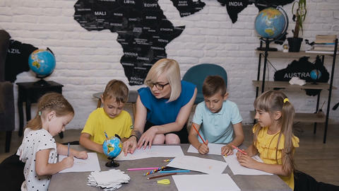 Primary school beautiful children drawing in the classroom with teacher helping Footage