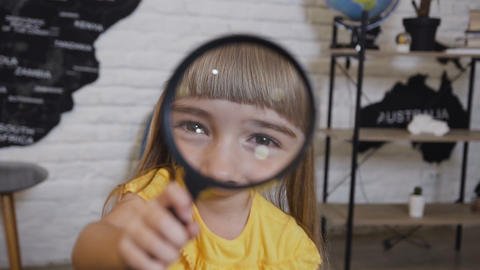 Portrait of a cute girl who playing looking in magnifying glass. Cute little Live Action