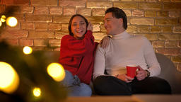 Laughing embracing caucasian couple sitting on sofa and watching movie with cup Footage