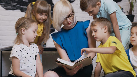 Caucasian teacher and her students sit on a small pillows read a book together Footage