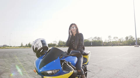 A young biker girl with dark hair in a leather jacket and sunglasses sits on her Footage