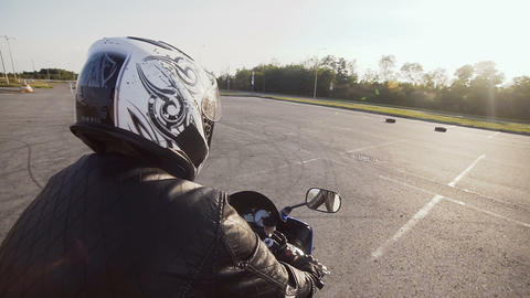 A young biker in a helmet rides on his motorcycle. Close-up Live Action