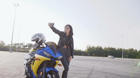Freedom and style. The biker girl stands next to her yellow and blue motorcycle Footage