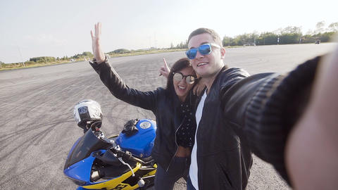 Two friends motorcyclists young guy and young girl wearing sunglasses do sephi Live Action