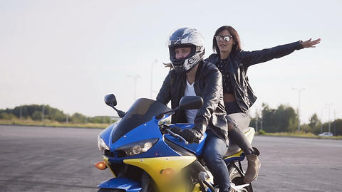 A young man and a young woman dressed in stylish clothes have fun riding a Live Action