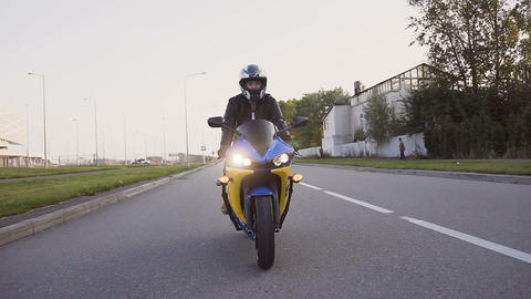 A young biker in a leather jacket and a helmet riding at the motorcycle along Live Action