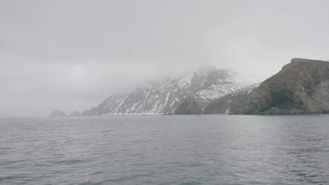 Panoramic landscape snowy mountains and cliffs in misty haze in ocean Footage