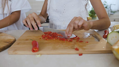 Close-up of a female hands cutting red hot pepper on cutting board at home in Live Action