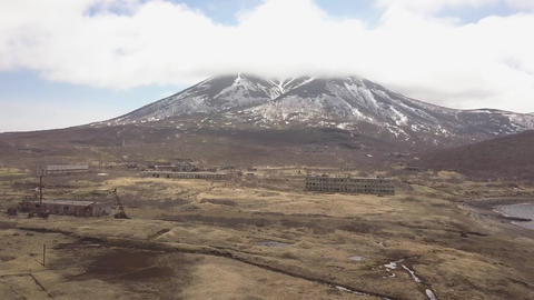 Abandoned building in destroyed city in mountain with snowy peaks aerial ビデオ