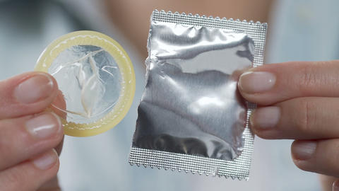 Woman fingers taking condom from package, birth control device, safe sex life Footage