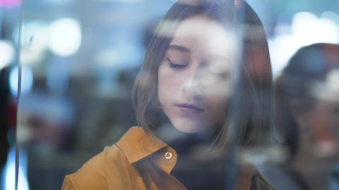 Blurred portrait of a beautiful young woman in glass store glares Rack focus 영상물