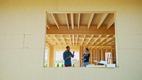 Two Young People Discussing Construction of a House GIF