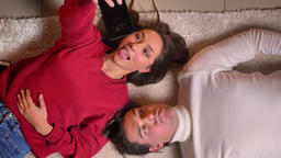 Top shot of young couple lying head to head on carpet and making funny selfie ビデオ